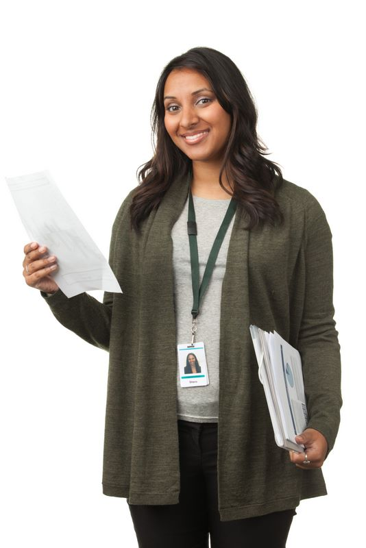 Woman with clipboard in hand smiling.