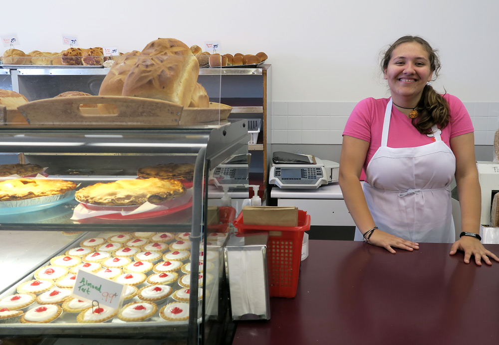 Smiling woman behind a bakery counter