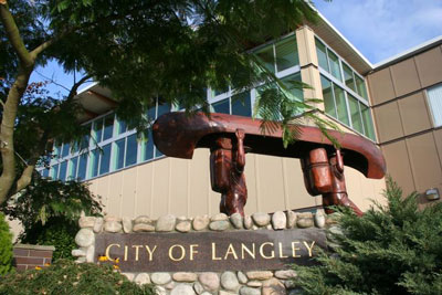 Exterior of Langley library and city hall with wooden carving of two people carrying a canoe