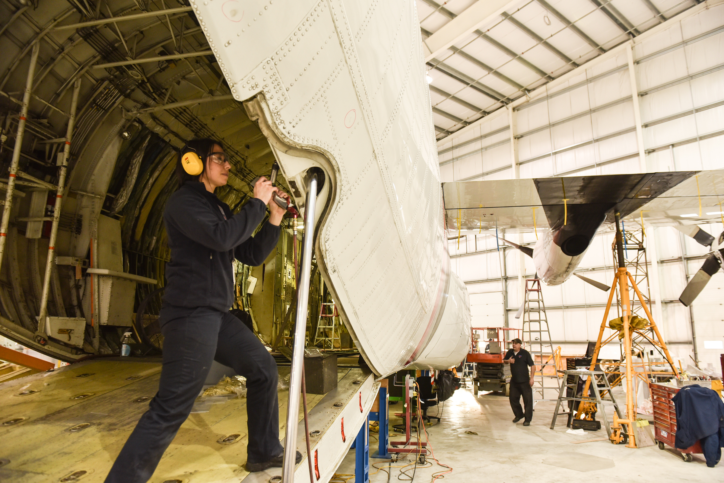 Woman working on the interior of an airplane in a hangar
