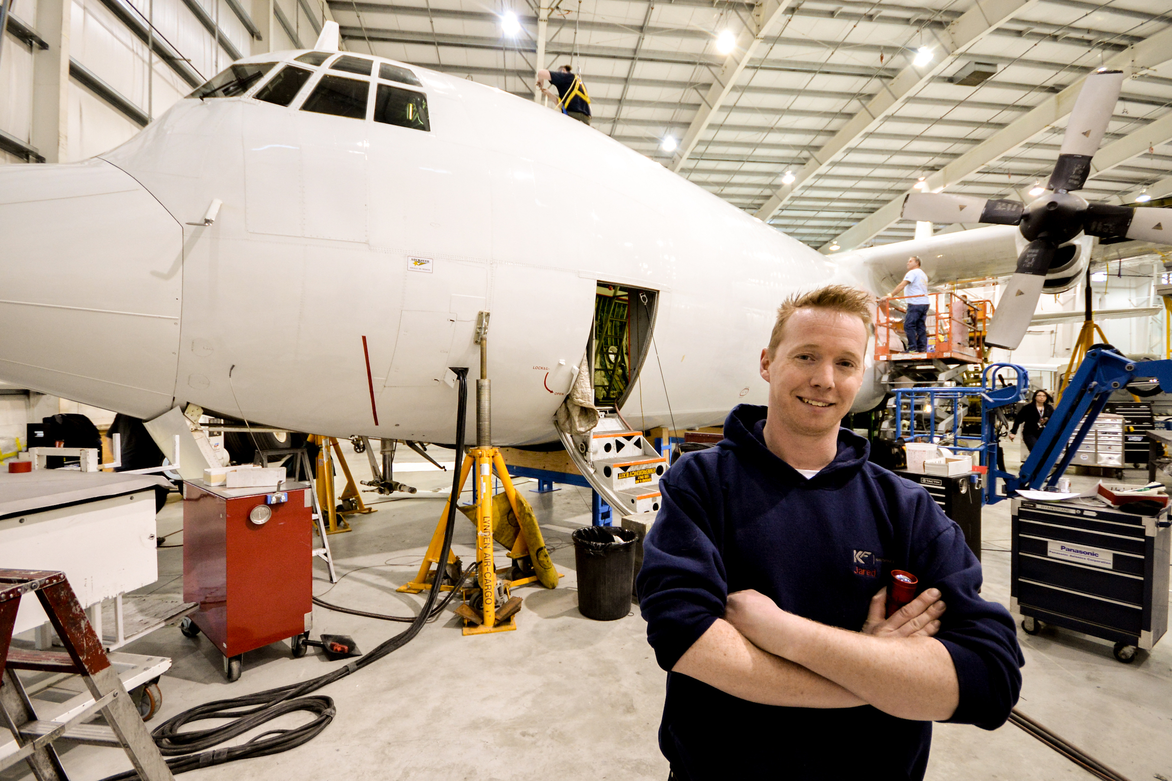 Man standing in front of an airplane being built in an hangar