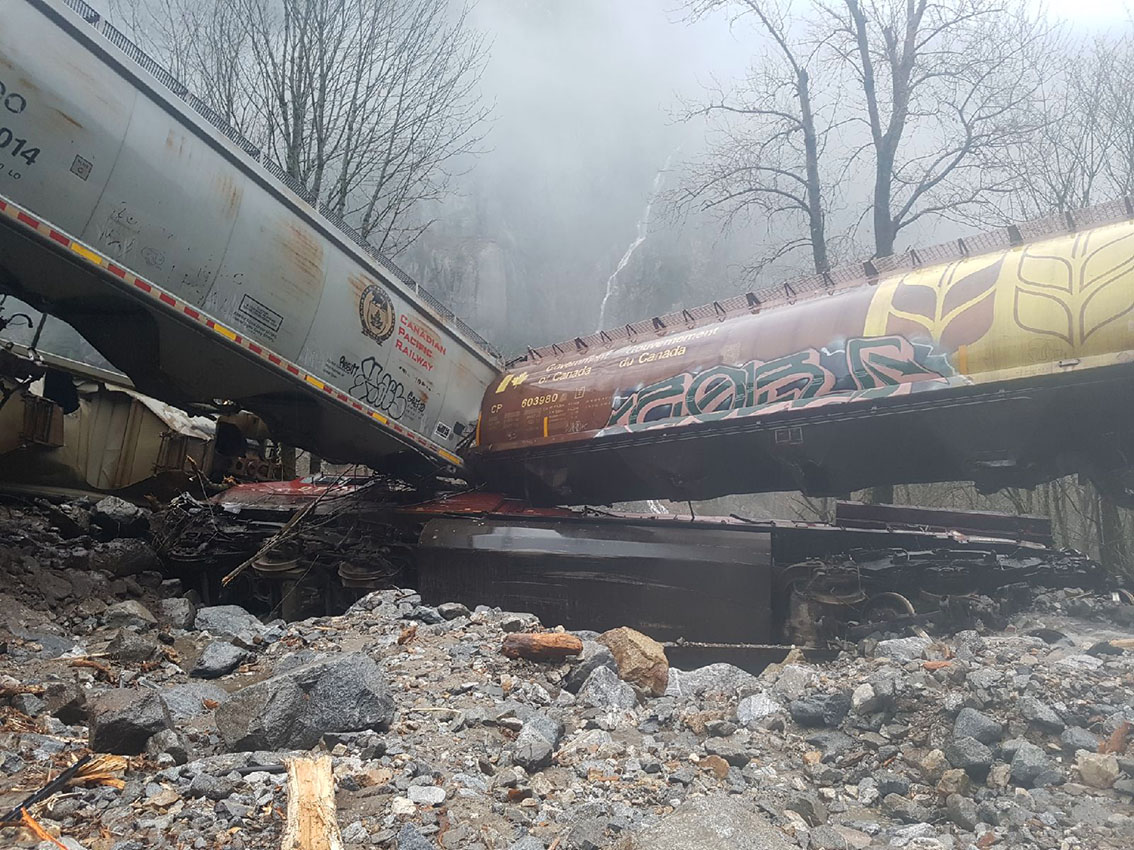 A rock slide caused a CP Rail train to derail. This picture shows two empty grain train cars on top of the CP Rail train engine car buried in rocks