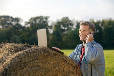 farmer in a field, speaking on a cell phone, with an open laptop on a hay bale.