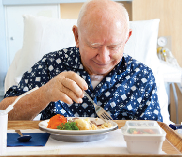 Man in hospital bed eating a meal